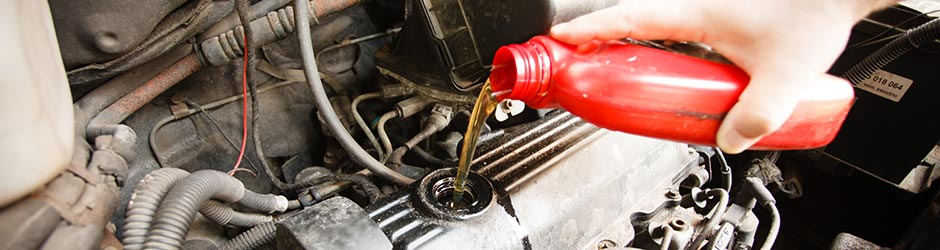 Car having oil poured into it's engine as part of a service at Quayside Motor Engineers in Southampton - Car Servicing Southampton